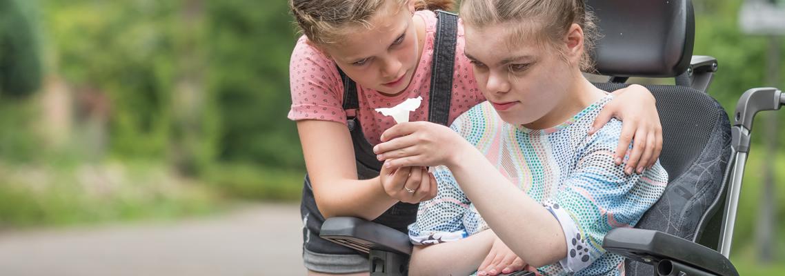 Young Carer. Ein Mädchen hilft der Schwester mit einer Behinderung