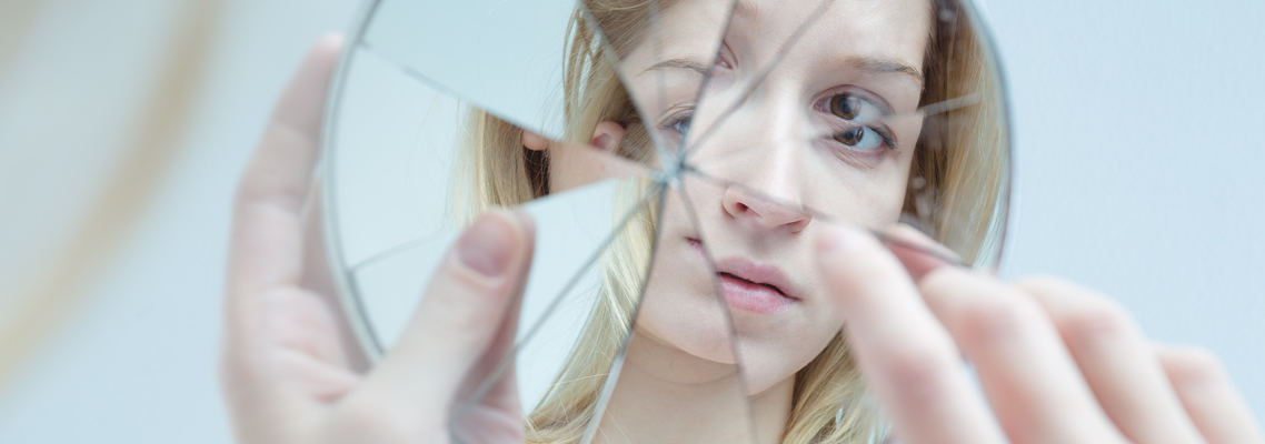Eine junge Frau schaut sich in einem gebrochenen Spiegel