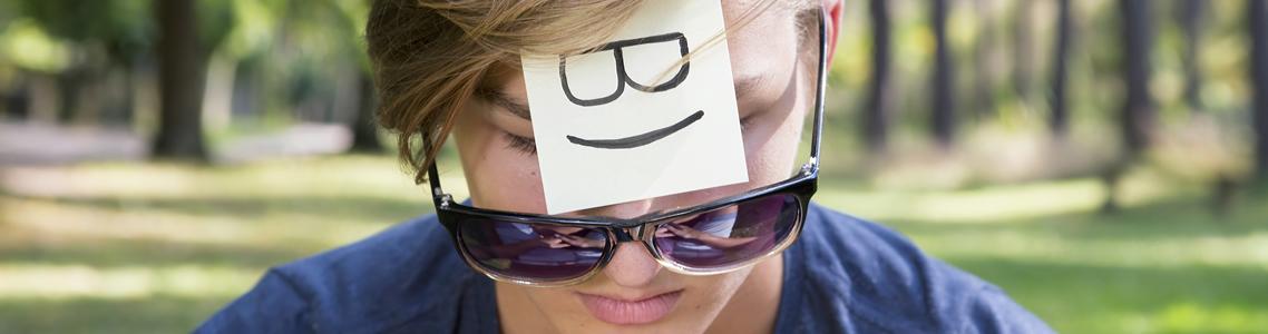 Junger Mann mit positiven und mit negativen Gedanken